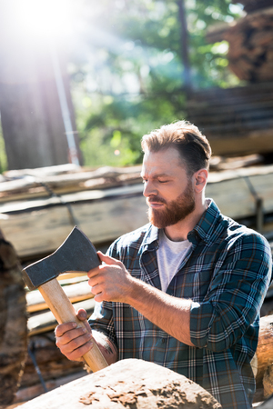 bearded lumberjack in checkered shirt  touching blade of axe at sawmill