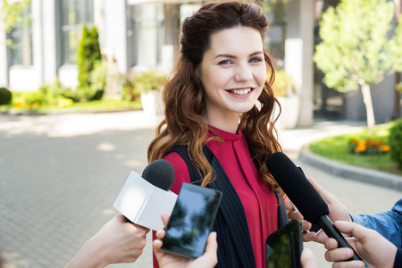 journalists interviewing public successful businesswoman with microphones and smartphones Stock Photo