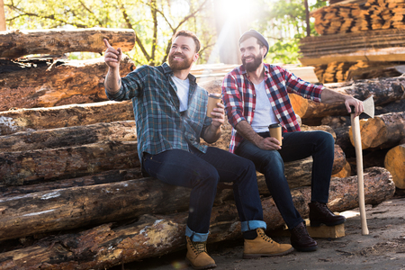 smiling lumberjack with coffee cup pointing by finger to partner with axe sitting on logs at sawmill 스톡 콘텐츠