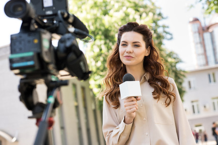 beautiful female journalist with microphone talking to digital video camera Stock Photo