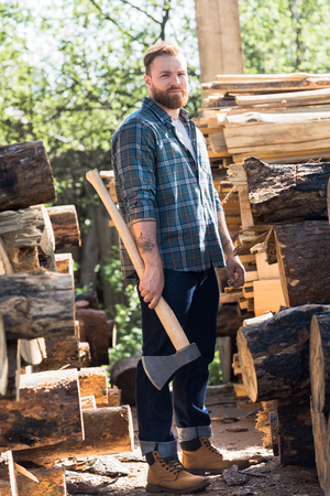 bearded lumberjack  in checkered shirt standing with axe at sawmill Zdjęcie Seryjne