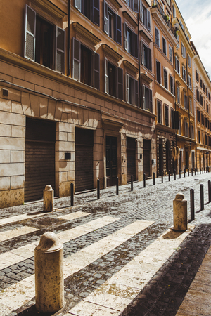 street with ancient buildings and cobbled road on street of Rome, Italy Stock fotó