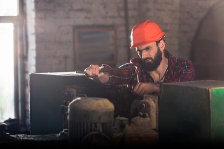 serious worker in protective helmet repairing machine tool at sawmill Zdjęcie Seryjne
