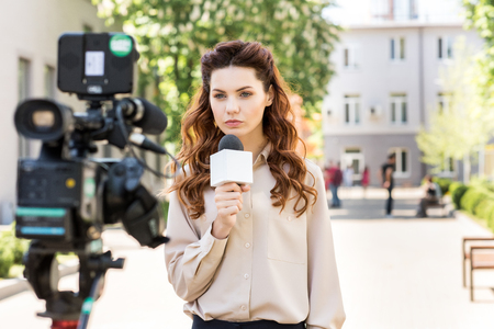 serious anchorwoman with microphone standing in front of digital video camera
