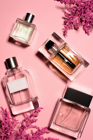 top view of bottles of perfumes with pink flowers