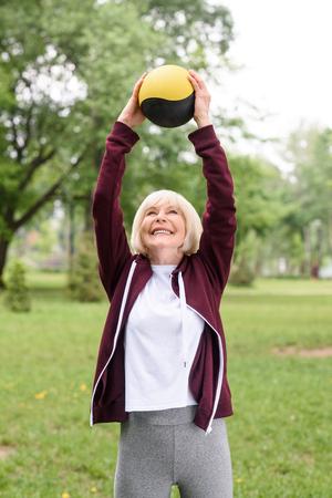 elderly sportswoman exercising with medicine ball in green park