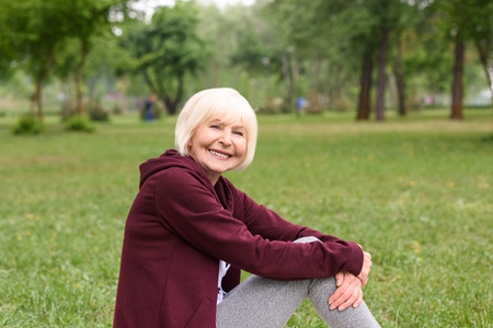 cheerful senior woman sitting on green grass in park