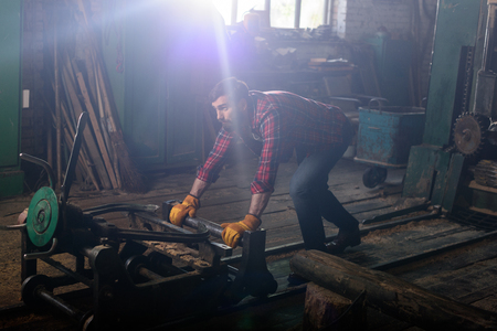 bearded worker in protective gloves pushing machine at sawmill Stock fotó