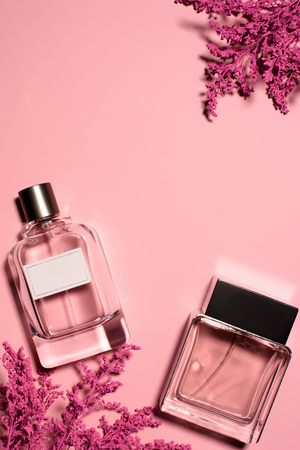 top view of bottles of perfumes with pink branches on pink surface Banco de Imagens