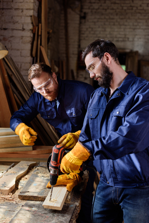 craftsman pointing to partner in protective gloves and googles working with electric drill at carpentry Stock Photo