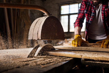 cropped image of carpenter in protective gloves  using machine saw at sawmill Stock Photo