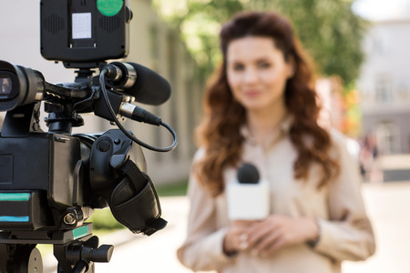 selective focus of journalist with microphone standing in front of digital video camera