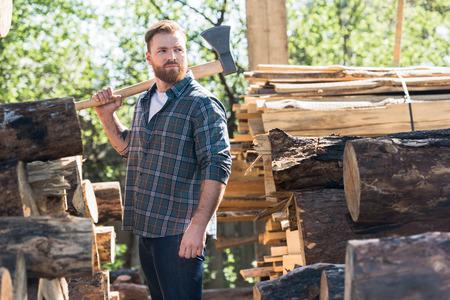 Holzfäller im karierten Hemd mit Axt auf der Schulter zwischen den Stämmen im Sägewerk