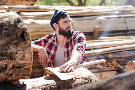 bearded lumberjack in checkered shirt with axe looking away at sawmill