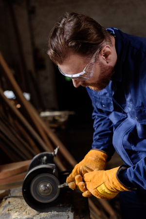 worker in protective googles and gloves using grinding machine at sawmill Zdjęcie Seryjne