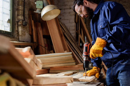 bearded craftsman in protective gloves and googles drilling wooden plank at carpentry