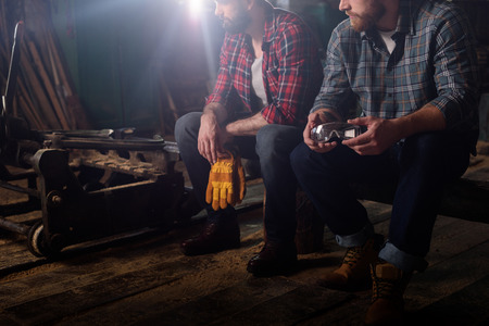 cropped shot of two workers holding protective gloves and googles at sawmill Stock Photo