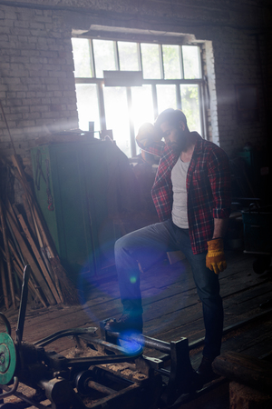 bearded worker in protective gloves wiping forehead and standing near machine at sawmill Stock Photo