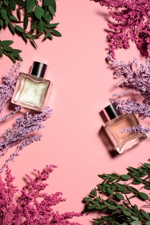 top view of glass bottles of perfumes with flowers on pink surface Фото со стока