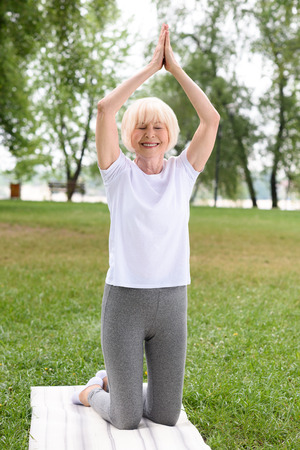 senior woman with namaste gesture practicing yoga on mat in park Imagens