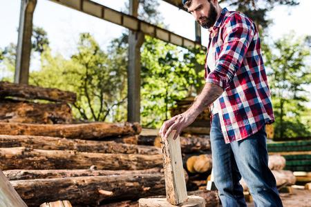 lumberjack in checkered shirt preparing to chop half of log at sawmill