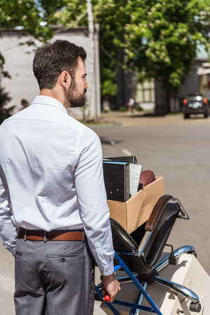 rear view of fired young manager with boxes on trolley cart Stock Photo