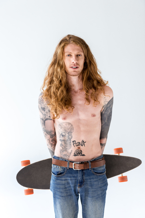 handsome shirtless tattooed sportsman with ginger hair standing with longboard isolated on white