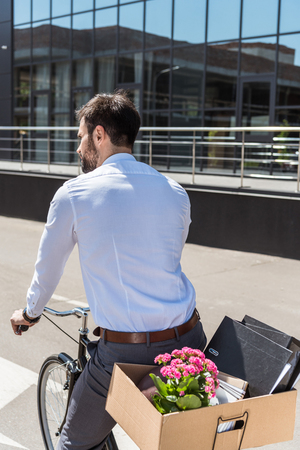rear view of young manager riding on bicycle with box on trunk