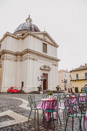 CASTEL GANDOLFO, ROME SUBURB, ITALY - MARCH 14, 2018: ancient historical St Thomas of Villanova Church and cafe tables