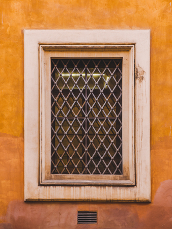 window with grating on old building in Rome, Italy
