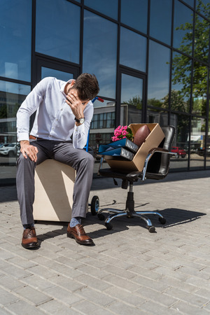 young depressed manager with box of personal stuff sitting on chair outdoors after he was fired
