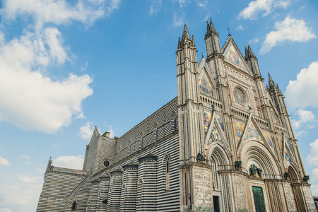 low angle view of ancient Orvieto Cathedral against blue sky in Orvieto, Rome suburb, Italy