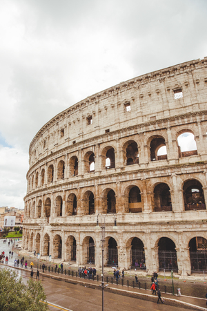 ROME, ITALY - 10 MARCH 2018: Colosseum ruins with tourists passing by on cloudy day Banco de Imagens