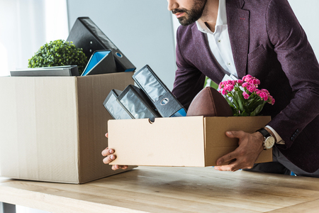 cropped shot of fired young businessman taking box of personal stuff from desk at office