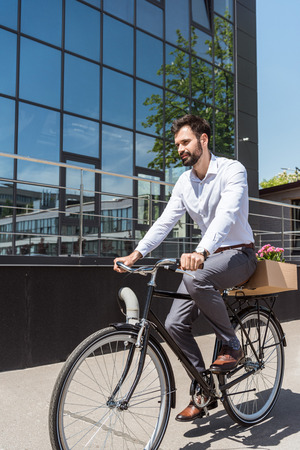 young happy manager riding on bicycle with box on trunk