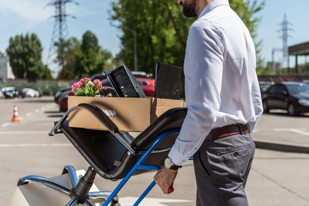 cropped shot of fired young manager with boxes on trolley cart at parking Stock Photo