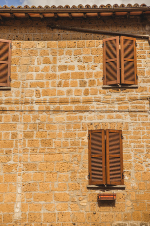 facade of old building with shuttered windows in Orvieto, Rome suburb, Italy Фото со стока