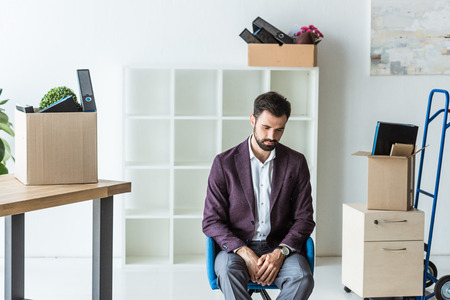 depressed fired businessman sitting on chair in office with boxes of personal stuff Stock Photo