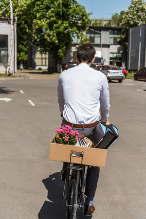 rear view of manager riding on bicycle with box of personal stuff on trunk 版權商用圖片