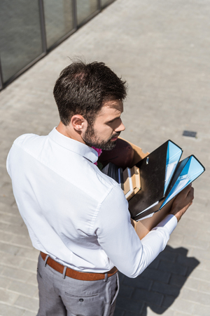 high angle view of young manager with box of folders and book outdoors