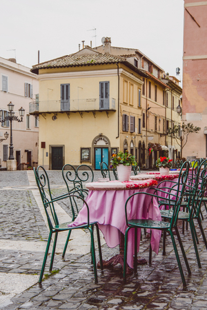 empty cafe tables on street after rain in Castel Gandolfo, Rome suburb, Italy