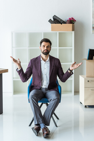 bewildered young businessman sitting on chair in office after he gets fired Stock fotó
