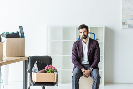 fired young businessman with boxes of personal stuff sitting on trolley cart