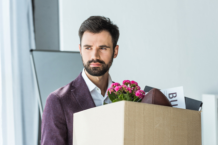 depressed young businessman carrying box of personal stuff after he gets fired