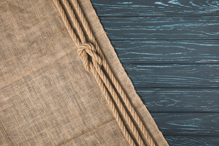 top view of knotted brown nautical rope on sackcloth on wooden background Imagens