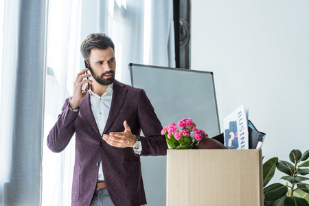 fired young businessman talking by phone near box of personal stuff at office