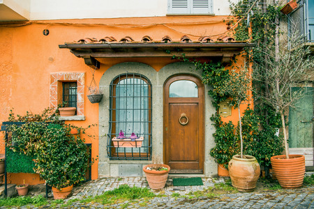 facade of beautiful building with potted plants and flowers in Castel Gandolfo, Rome suburb, Italy