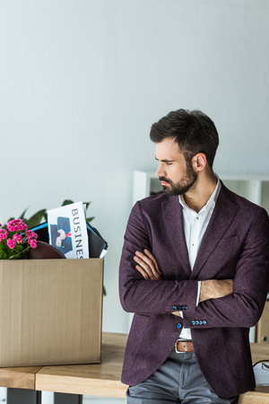 thoughtful young businessman looking at box of personal stuff in office after he gets fired