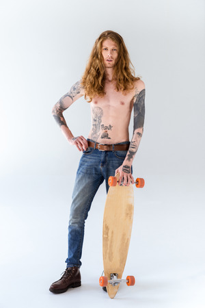 handsome shirtless tattooed sportsman with curly hair standing with longboard on white
