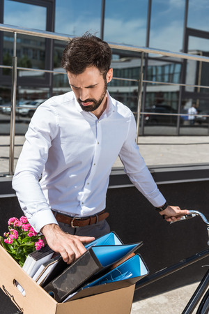 young manager putting box of personal stuff on bicycle trunk